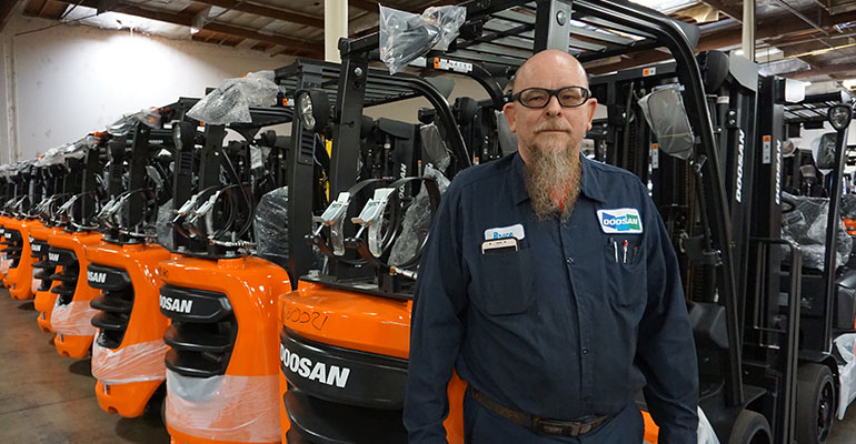 a service tech standing in front of forklifts